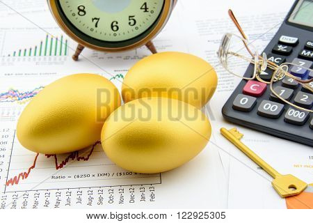 Three golden eggs with a golden key a calculator eye glasses and a clock on business and financial summary reports. A long term sustainable growth investment concept.