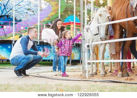 Mother, father and daughter with cotton candy stroking pony in amusement park, family at fun fair