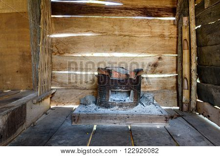 Traditional charcoal burning clay stove in a rustic wooden house.