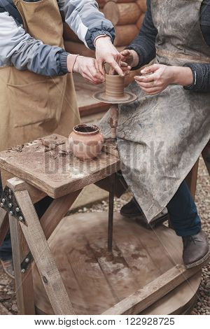 The hands of a potter help make a pitcher on a pottery wheel. Two men with hands caked in clay. One man teaches the second pottery.