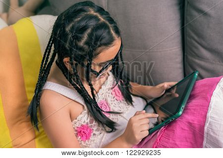 Cute little girl, dreadlocks hair style ,playing with computer at home laying on sofa ** Note: Shallow depth of field