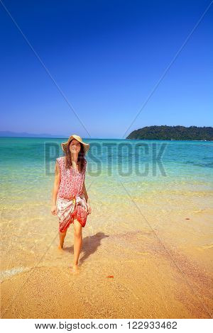 young woman with casual dress an sunhat on the beach.