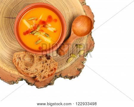 Bowl Of Pumpkin Soup On Wood Cut Over White