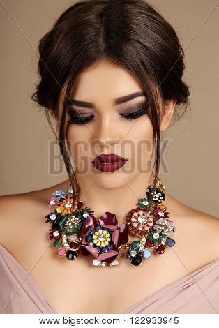 fashion studio portrait of gorgeous young woman with dark hair and evening makeup, with luxurious necklace