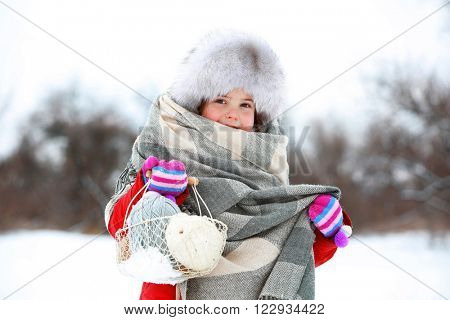 Little girl holding basket with skeins in snowy park outdoor