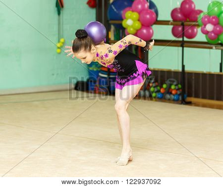 Young Female Gymnast Doing Crafty Trick With Ball On Art Gymnastics Performance