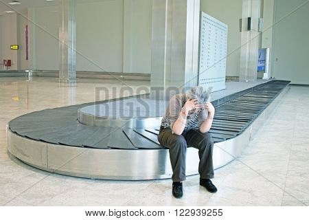 lost luggage - female tourist upset over luggage lost sitting alone on luggage carousel with hands on her head