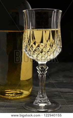 Closeup of a white wine bottle and glass on black slate. Vertical format.