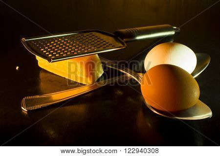 Eggs , grater , spoons , parmigiana isolated on black  background