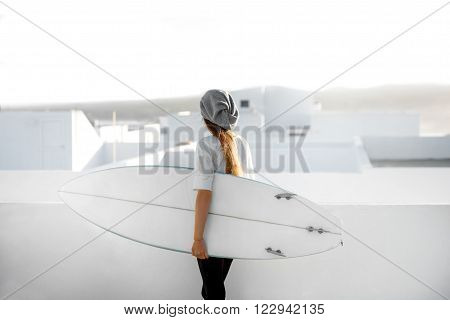 Young woman in white t-shirt and hat standing with surfboard on the roof top on the white city background. Enjoying morning sunlight and preparing for surfing
