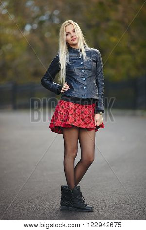 Young cute trendy dressed blonde woman strolling autumnal park posing outdoors against blurry foliage background
