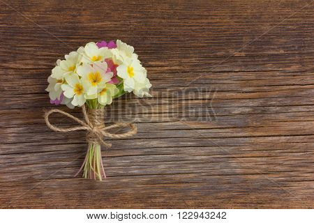a bunch of pale yellow primroses tied with string on an old wooden board in the cracks. Free space for text. Copy space.