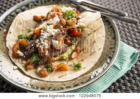 Beef burrito with chill greens, feta & refried beans