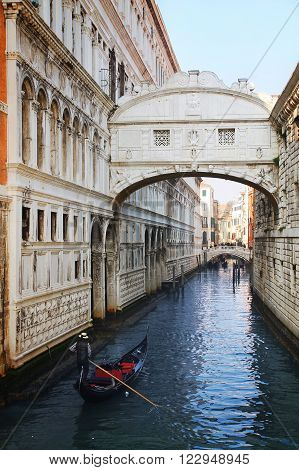 gondola sails under the Bridge of Sighs in Venice Italy