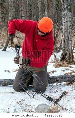 Trapper preparing a trap for a winter water set