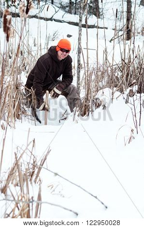 Trapper setting water traps in the winter