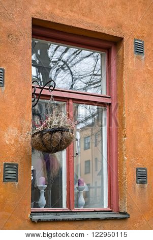 Window in a house in a narrow street in Stockholm decorated of ornamental flowerpot with flower.