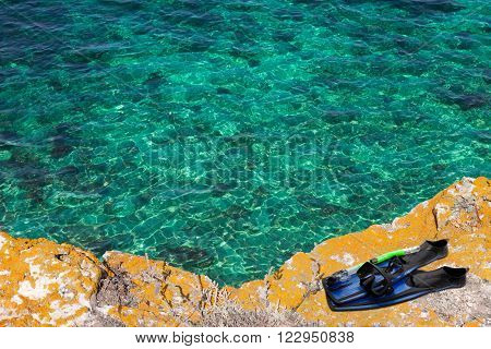 Mask, snorkel and flippers on the cliff of sea in sun day