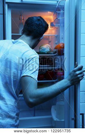 Man looking for food in refrigerator at nighttime