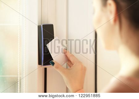 Woman setting control panel on security system at home