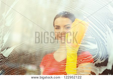 Young woman washing window glass with duster inside