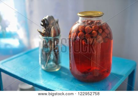 three-liter glass jar with strawberry compote canned on blue table