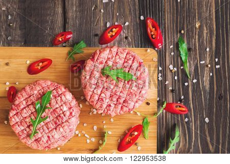 Raw ground beef burgers with chili pepper and arugula on rustic wooden background. Top view.