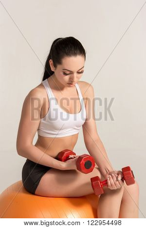 Young beautiful sportswoman in white top and black shorts with dumbbells exercising on fitball.