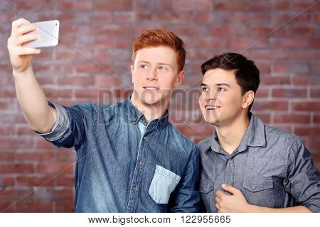 Two teenager boys making photo by their self with mobile phone on brick wall background