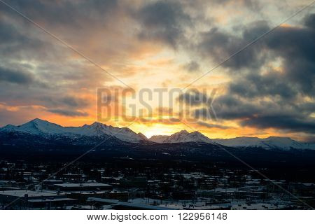 Bright colorful sunrise behind mountains with dark snow clouds over Anchorage Alaska