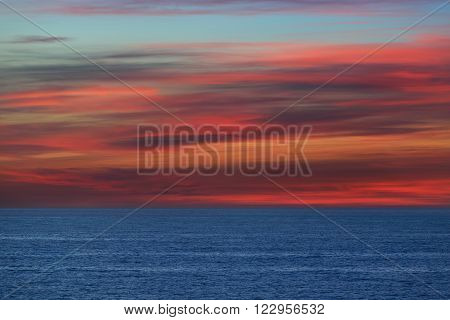 Open Baltic sea. Striped red and orange beautiful clouds at sunset