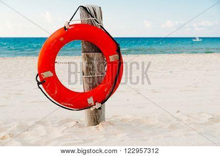 Life buoy on a pole on a sandy beach with blue ocean water
