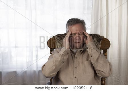 Elderly man holding his hands to his head as he suffers from a headache or migraine. Sitting at home in a rocking chair