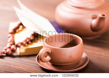 Ceramic tea-things beads and the book on a wooden table. Close up small depth of sharpness