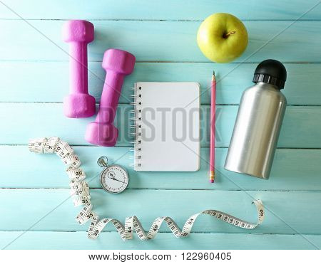 Athlete's set with equipment, notebook and bottle of water and apple on blue wooden background