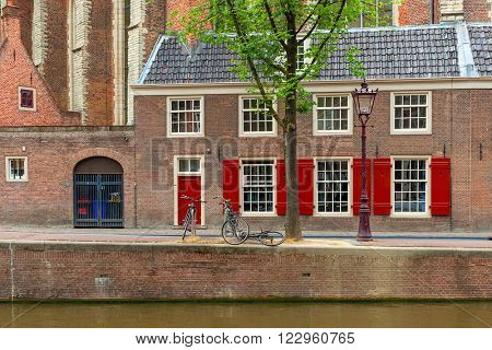 Bicycles on narrow street between canal and brick house in Amsterdam, Netherlands.