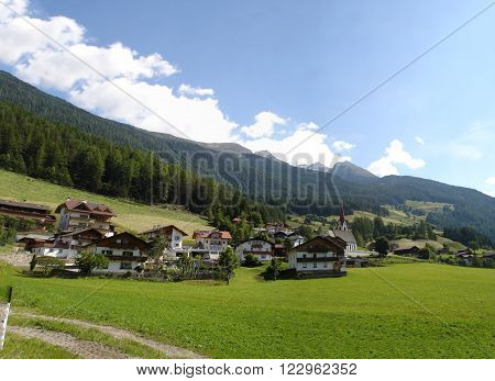Mountain village Ahornach on a mountain plateau in the Nature Park Rieserferner-Ahrn in South Tyrol, Italy; green meadows and wooded mountais, blue sky with white clouds