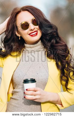 Indoor fashion spring portrait of elegant sexy woman in luxury bright glamour outfit, red lips, trendy yellow jacket and trendy sunglasses.Model holding coffee cup, listen music, smiley woman, crazy, toned