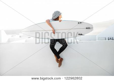 Young smiling woman in white t-shirt and hat sitting with surfboard on the roof top on the white city background. Enjoying morning sunlight and preparing for surfing