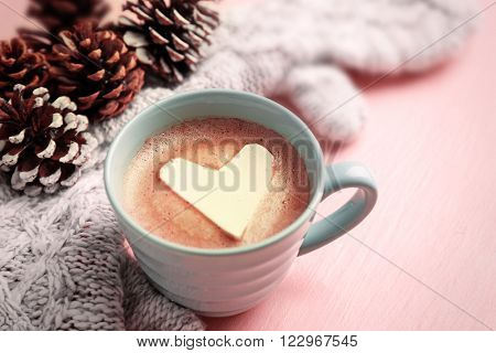 Cup of hot cappuccino with heart marshmallow, warm mittens and pine cones on pink background