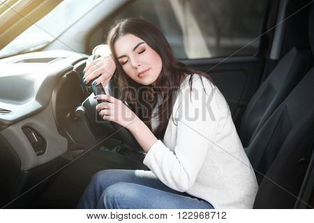 Tired young woman asleep on steering wheel in her car.