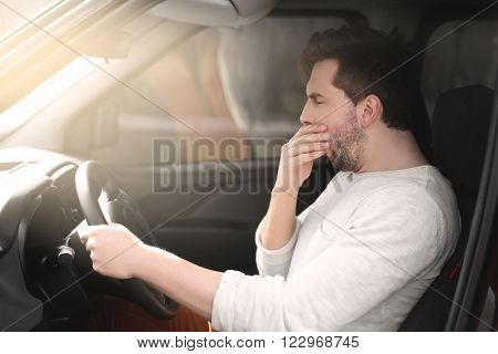 Tired young man driving his car.