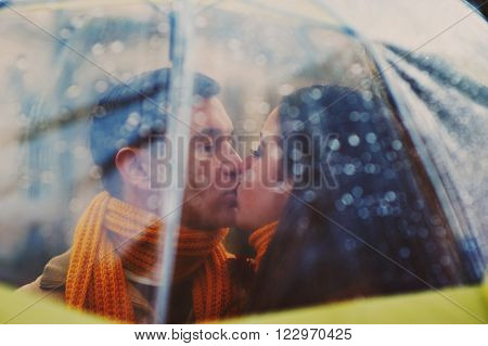 Closeup of young beautiful couple kissing under the umbrella in an autumn rainy day