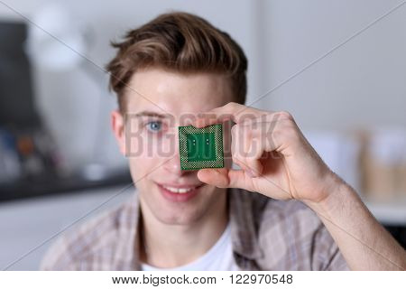 Young man holding computer processor near eye
