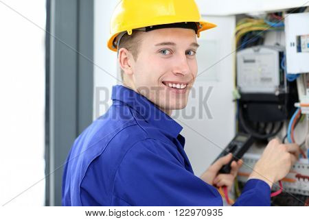 Young electrician measuring voltage in fuse board