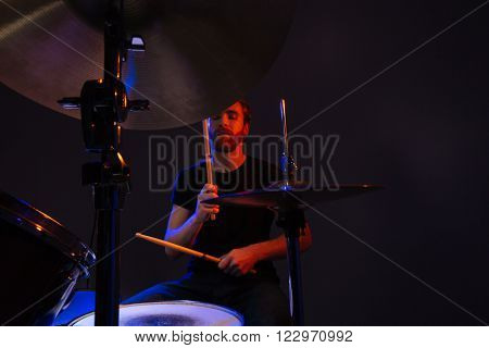 Attractive bearded man drummer with closed eyes enjoying playing drums over dark background