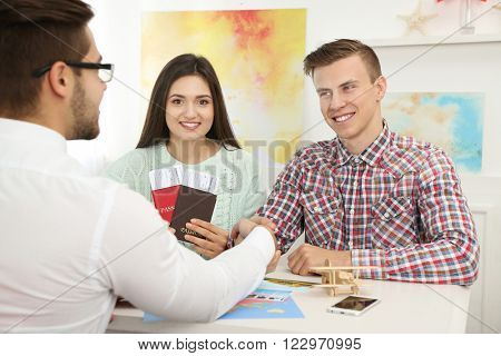 Agent and young couple handshaking in the office of travel company