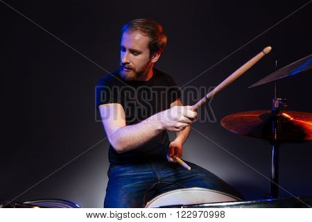 Bearded young man drummer with closed eyes sitting and playing drums over dark background