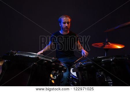 Attractive concentrated bearded man drummer playing his kit over dark background