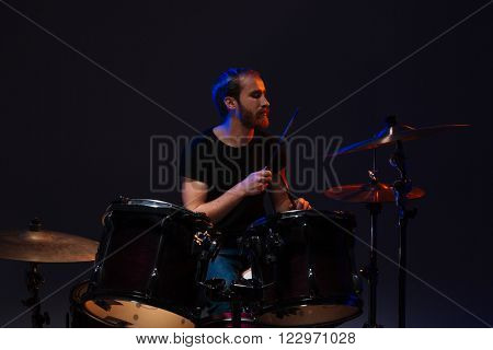 Handsome bearded man drummer playing his kit over dark background